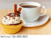 Cup of coffee and cupcake with cream and decorative chocolate sprinkles, cinnamon and anise. Стоковое фото, фотограф Анна Гучек / Фотобанк Лори