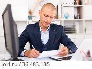 Upset young businessman working documents and laptop. Стоковое фото, фотограф Яков Филимонов / Фотобанк Лори