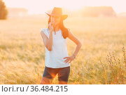 Woman farmer in cowboy hat standing and smiling at agricultural field... Стоковое фото, фотограф Zoonar.com/Max / easy Fotostock / Фотобанк Лори