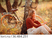Happy active young woman riding vintage bicycle in autumn park at... Стоковое фото, фотограф Zoonar.com/Max / easy Fotostock / Фотобанк Лори