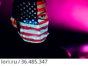 Adult man in medical face mask with USA flag on his face in the dark. Стоковое фото, фотограф Zoonar.com/Max / easy Fotostock / Фотобанк Лори