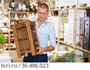 Man holding wooden chest of drawers at store. Стоковое фото, фотограф Яков Филимонов / Фотобанк Лори