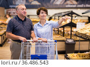 Mature couple husband and wife choose bakery products in the grocery section in supermarket. Стоковое фото, фотограф Татьяна Яцевич / Фотобанк Лори