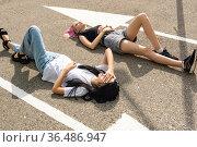 Two teenage girls have fun lying on an empty road parallel to the markings. Стоковое фото, фотограф Евгений Харитонов / Фотобанк Лори