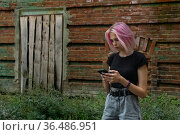 Teen girl writes or reads a message using the phone against the background of an old wall. Стоковое фото, фотограф Евгений Харитонов / Фотобанк Лори