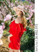 Cheerful girl posing in a red dress in spring blooming garde. Стоковое фото, фотограф Яков Филимонов / Фотобанк Лори