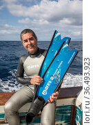 Photographer Franco Banfi on board boat holding long free diving fins / flippers during sperm whale photography trip , Dominica, Caribbean Sea, Atlantic Ocean. 2019. Стоковое фото, фотограф Franco Banfi / Nature Picture Library / Фотобанк Лори