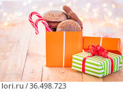 Ton of colorful gifts, one opened full with gingerbread and Xmas candies... Стоковое фото, фотограф Zoonar.com/Andrei Ureche / easy Fotostock / Фотобанк Лори
