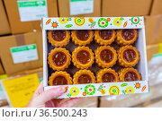 Russia, Samara, June 2021: a man's hand holds a package of shortbread cookies with jam in a store. Редакционное фото, фотограф Акиньшин Владимир / Фотобанк Лори