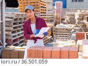 Asian female worker keeps records of ceramic tiles. Стоковое фото, фотограф Яков Филимонов / Фотобанк Лори