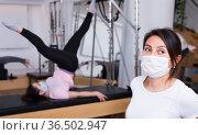 Gym woman protective mask pilates stretching in reformer bed. Стоковое фото, фотограф Яков Филимонов / Фотобанк Лори