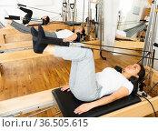 Women doing pilates exercises lying on pilates machines. Стоковое фото, фотограф Яков Филимонов / Фотобанк Лори
