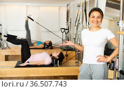 Young Hispanic female fitness instructor in pilates reformer studio. Стоковое фото, фотограф Яков Филимонов / Фотобанк Лори
