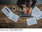 Businessman working on laptop with financial documents, top view. Стоковое фото, фотограф Zoonar.com/Tatiana Badaeva / easy Fotostock / Фотобанк Лори