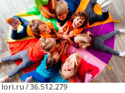 Lovely children laying on multicolor canopy in circle. Team building... Стоковое фото, фотограф Zoonar.com/OKSANA SHUFRYCH / easy Fotostock / Фотобанк Лори