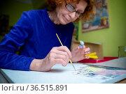 Happy elderly woman painting for fun at home. Senior Caucasian senior... Стоковое фото, фотограф Zoonar.com/Yelizaveta Tomashevska / easy Fotostock / Фотобанк Лори