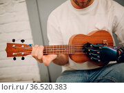 Young disabled man with artificial prosthetic hand plays on Ukulele... Стоковое фото, фотограф Zoonar.com/Max / easy Fotostock / Фотобанк Лори