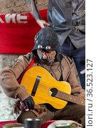 World after nuclear war. Last embroiderer plays the guitar. Стоковое фото, фотограф Евгений Ткачёв / Фотобанк Лори