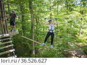 A young woman works hard to cross a challenging treetop rope course... Стоковое фото, фотограф Lori Epstein / age Fotostock / Фотобанк Лори