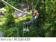 A woman enjoys the challenge of a treetop zipline on a hot summer... Стоковое фото, фотограф Lori Epstein / age Fotostock / Фотобанк Лори