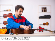 Young male repairman repairing musical instruments at workplace. Стоковое фото, фотограф Elnur / Фотобанк Лори