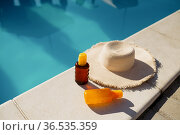 Beverage in glass and hat at the edge of the pool. Стоковое фото, фотограф Tryapitsyn Sergiy / Фотобанк Лори