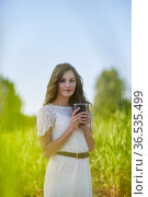 Young blonde woman in white dress with coffee cup is standing in a tall grass.. Стоковое фото, фотограф Serg Zastavkin / Фотобанк Лори