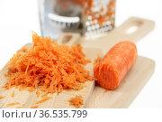 Натертая на терке морковь, лежащая на деревянной разделочной доске. Стоковое фото, фотограф Румянцева Наталия / Фотобанк Лори
