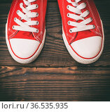 Pair of red textile sneakers with white laces on a brown wooden background... Стоковое фото, фотограф Zoonar.com/Danko Natalya / easy Fotostock / Фотобанк Лори