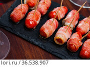 Sausage rolled with bacon on black dish. Стоковое фото, фотограф Яков Филимонов / Фотобанк Лори