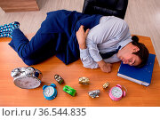Young businessman sleeping in the office in time management concept. Стоковое фото, фотограф Zoonar.com/Elnur Amikishiyev / easy Fotostock / Фотобанк Лори