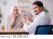 Old male patient visiting young male doctor dentist. Стоковое фото, фотограф Elnur / Фотобанк Лори