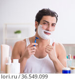 Young handsome man shaving early in the morning at home. Стоковое фото, фотограф Elnur / Фотобанк Лори