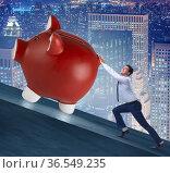 Man pushing piggybank uphill in business concept. Стоковое фото, фотограф Elnur / Фотобанк Лори