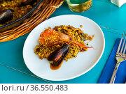 Delicious traditional Valencian seafood paella - savory rice dish with shrimps and clams. Стоковое фото, фотограф Яков Филимонов / Фотобанк Лори