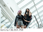 Two teen girls on the escalator in the mall. Стоковое фото, фотограф Евгений Харитонов / Фотобанк Лори