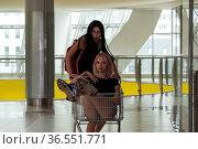 Two teenage girls are naughty in the mall, riding a shopping trolley. Стоковое фото, фотограф Евгений Харитонов / Фотобанк Лори