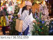 Positive woman choosing New Year's tree in christmas fair. Стоковое фото, фотограф Яков Филимонов / Фотобанк Лори