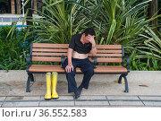 Singapore, Republic of Singapore, Asia - A man sits on a bench at... Редакционное фото, фотограф Olaf Schuelke / age Fotostock / Фотобанк Лори