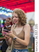 A caucasian teenage girl with curly hair uses her cell phone at a... Стоковое фото, фотограф Lori Epstein / age Fotostock / Фотобанк Лори