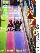 Two friends have fun sliding down a colorful slide at the county ... Стоковое фото, фотограф Lori Epstein / age Fotostock / Фотобанк Лори