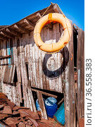 Old orange life saver hanged on edge of roof of shabby small wooden... Стоковое фото, фотограф Zoonar.com/KHALED ELADAWY / easy Fotostock / Фотобанк Лори