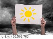Hände halten vor dunklen Wolken ein Blatt Paier mit einer aufgemalten... Стоковое фото, фотограф Zoonar.com/Desire for sunshine / easy Fotostock / Фотобанк Лори
