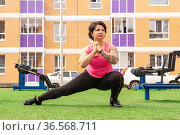 Young strong woman doing warm-up before workout on the sports ground with outdoor gym equipment in front of the house. Стоковое фото, фотограф Евгений Харитонов / Фотобанк Лори