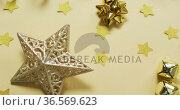 Video of gold christmas decorations with stars on yellow background. Стоковое видео, агентство Wavebreak Media / Фотобанк Лори
