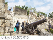 Macau, China. Visitors studying a cannon by the walls of the Portuguese... (2012 год). Редакционное фото, фотограф Ken Welsh / age Fotostock / Фотобанк Лори