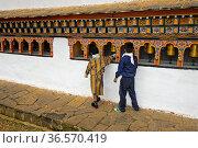 Zwei Kinder in traditioneller und westlicher Kleidung drehen Gebetsmühlen... Стоковое фото, фотограф Zoonar.com/Pant / age Fotostock / Фотобанк Лори