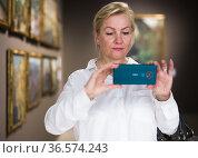 Female visitor taking picture in art gallery. Стоковое фото, фотограф Яков Филимонов / Фотобанк Лори
