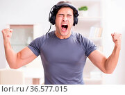 The man doing sports at home and listening to music. Стоковое фото, фотограф Zoonar.com/Elnur Amikishiyev / easy Fotostock / Фотобанк Лори