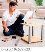 The man assembling shelf at home. Стоковое фото, фотограф Zoonar.com/Elnur Amikishiyev / easy Fotostock / Фотобанк Лори